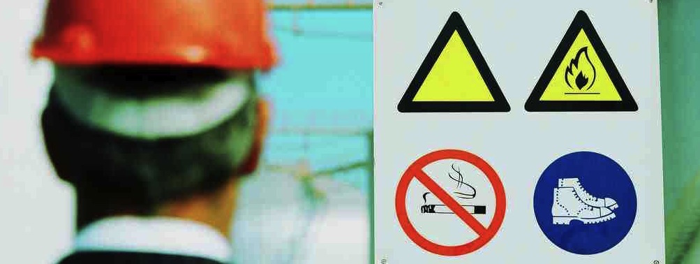 Man looking at health and safety sign in hard hat